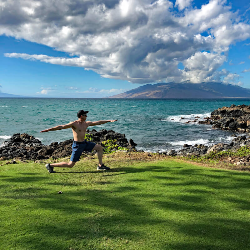 David doing a lunge by the ocean.