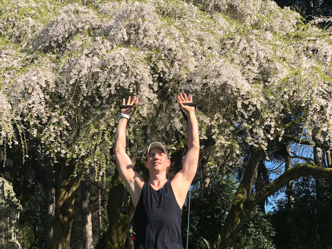 David working out under a cherry tree in blossom.